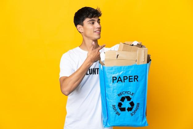 Homme tenant un sac de recyclage plein de papier à recycler sur mur jaune isolé pointant vers l'arrière