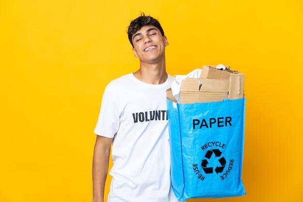 Homme tenant un sac de recyclage plein de papier à recycler sur mur jaune isolé en riant