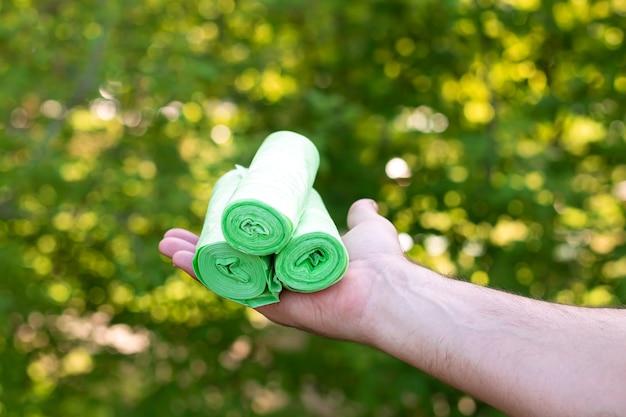 Homme tenant des sacs bio en plastique écologique en rouleaux à l'extérieur