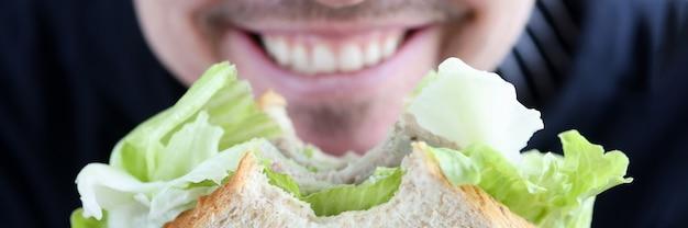 Homme tenant un sandwich dans les mains et souriant concept de régime alimentaire en gros plan