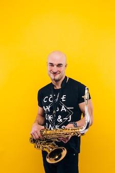 Un homme tenant un saxophone contre un mur jaune