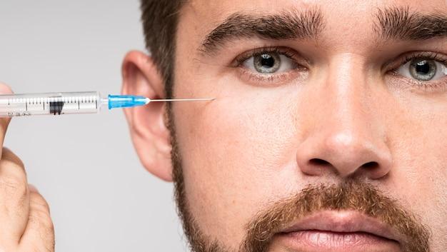 Homme tenant une seringue à côté de son visage