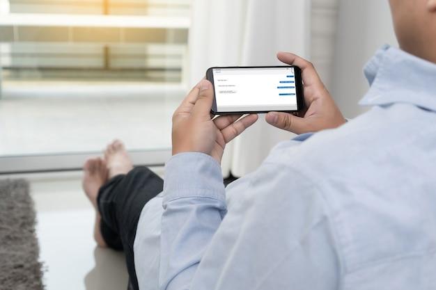 Homme tenant un smartphone à l'aide d'une application de messagerie