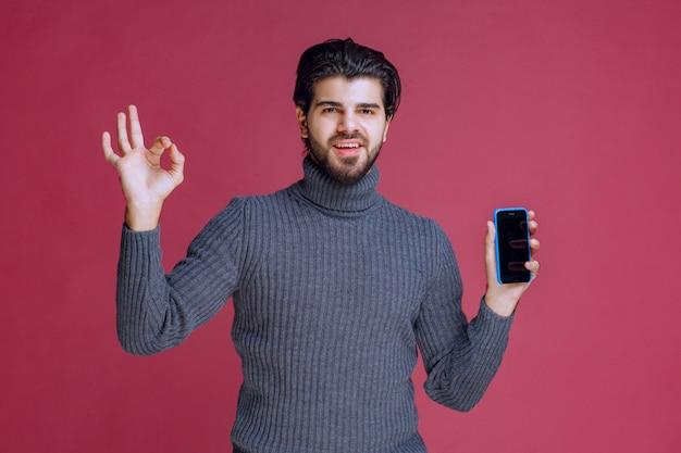 Homme tenant un smartphone et faisant un bon signe de la main.