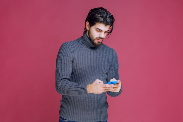 Homme tenant un smartphone, lire des messages ou envoyer des sms.