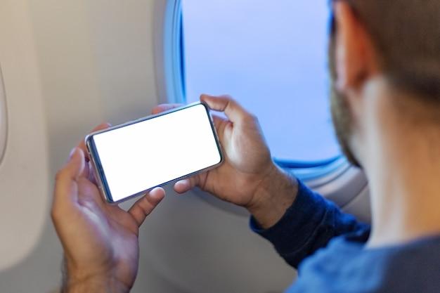 Homme tenant un smartphone maquette écran blanc dans les mains en avion.