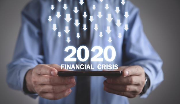 Homme tenant un smartphone avec un texte de crise financière 2020.