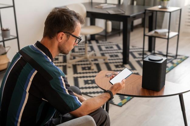 Homme tenant un smartphone tout en utilisant un haut-parleur intelligent