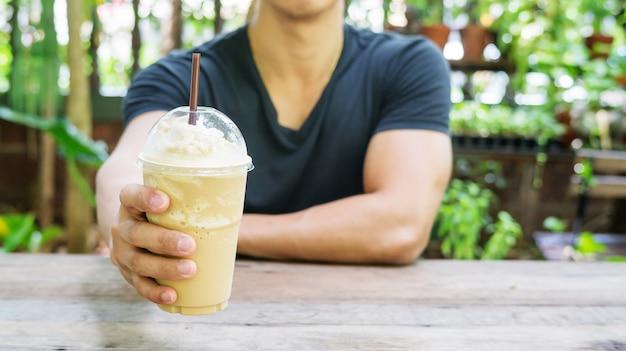 Homme tenant un smoothie au café sur un fond de plante.