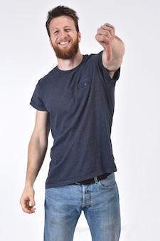 Homme tenant son pouce et grave sur blanc, souriant