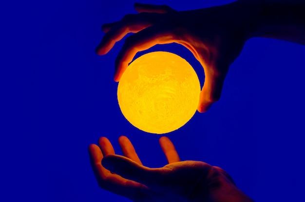 Homme tenant une sphère illuminée en forme de lune jaune.