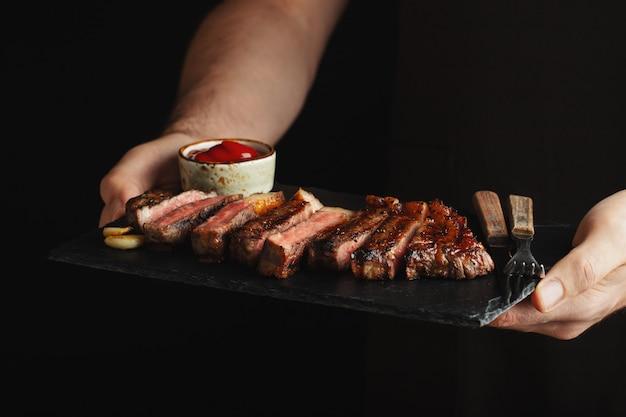 Homme tenant un steak de bœuf grillé juteux.