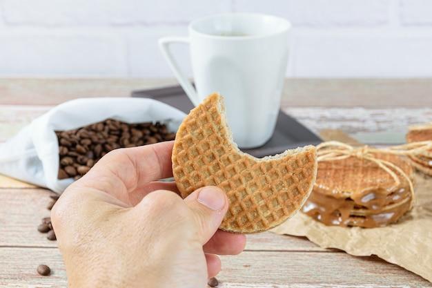 Homme tenant un stroopwafel avec une morsure. en arrière-plan des haricots et une tasse de café.