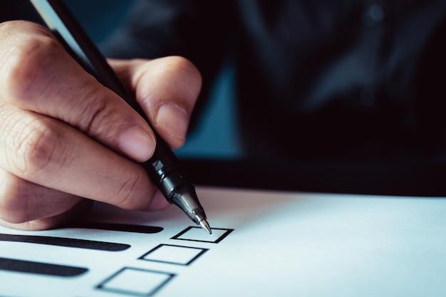 Homme tenant un stylo pour marquer sur papier de vote, concept de démocratie, ton rétro