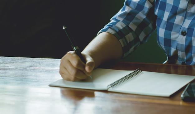 Homme tenant un stylo