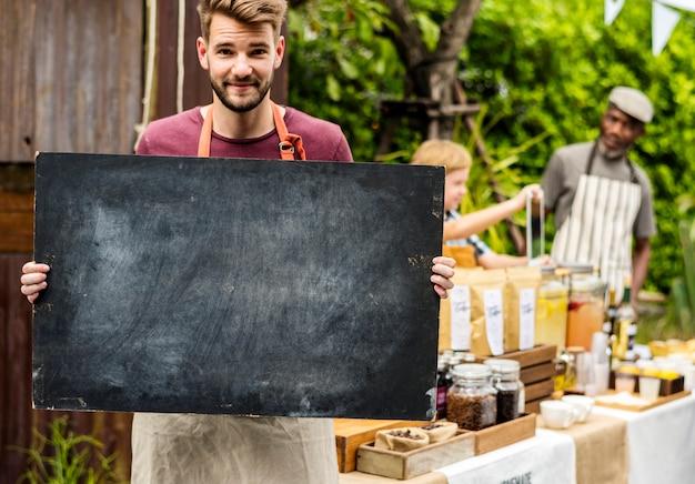 Homme tenant un tableau blanc au festival du marché des agriculteurs