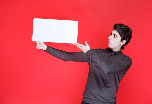 Homme tenant un tableau d'idées rectangulaire pour la présentation