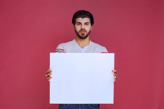 Homme tenant un tableau d'idées vide et faisant la présentation.