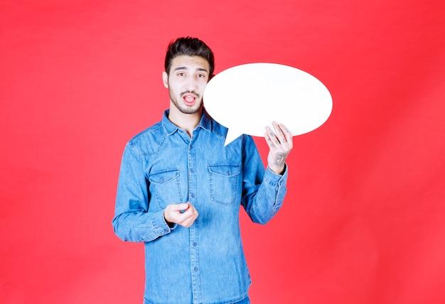 Homme tenant un tableau d'informations de forme ovale vierge et a l'air confus et réfléchi.
