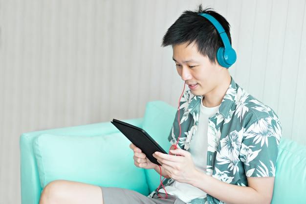Un homme tenant une tablette avec des écouteurs pour écouter de la musique dans le salon à la maison.