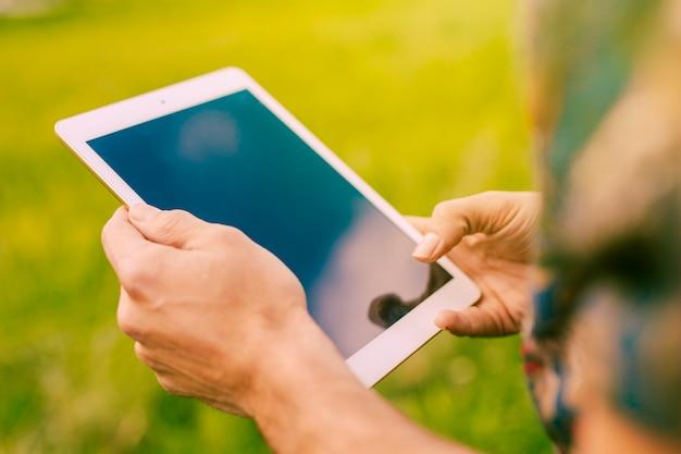 Homme tenant une tablette en milieu rural