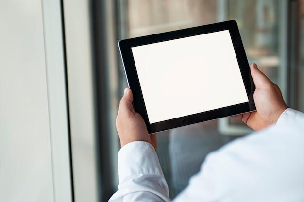 Homme tenant une tablette noire dans la main avec un écran blanc vierge