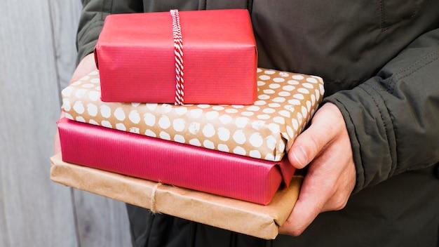 Homme tenant des tas de boîtes à cadeaux