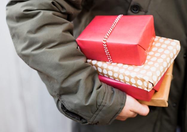 Homme tenant un tas de boîtes à cadeaux
