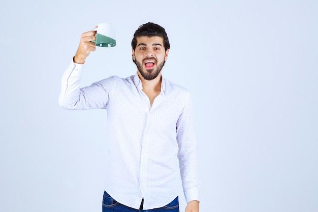 Homme tenant une tasse de boisson et se sentant satisfait