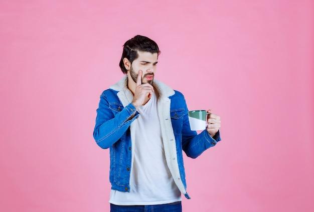 Homme tenant une tasse de café et a l'air pensif.