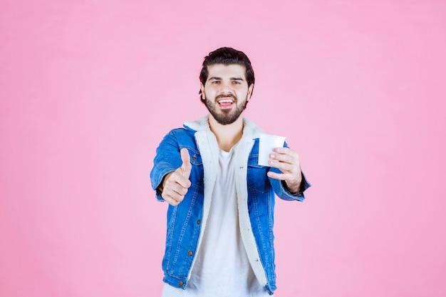 Homme tenant une tasse de café et appréciant le goût