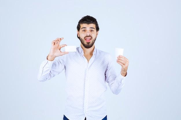 Homme tenant une tasse de café dans une main et présentant sa carte de visite dans une autre main