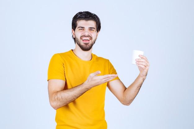 Homme tenant une tasse de café et faisant une présentation à l'aide de la main ouverte.