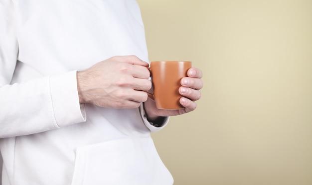Homme tenant une tasse de café sur fond jaune.