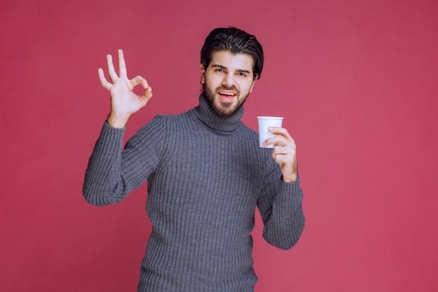 Homme tenant une tasse de café jetable et fait signe de plaisir.
