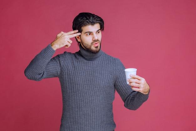 Homme tenant une tasse de café jetable et de la pensée.