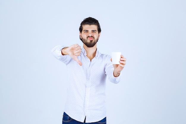Homme tenant une tasse de café et montrant le pouce vers le bas