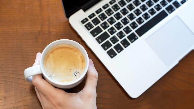 Un homme tenant une tasse de café, un ordinateur portable sur la table en bois. vue de dessus