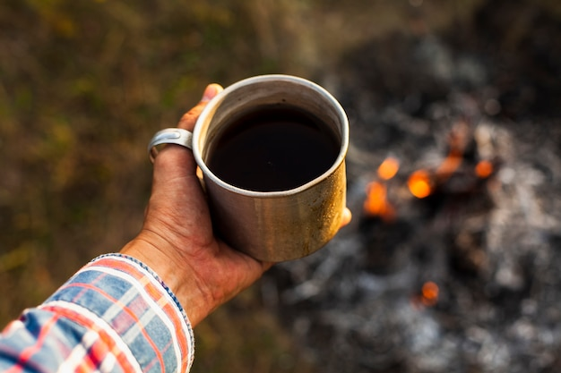 Homme tenant une tasse de café préparé en plein air