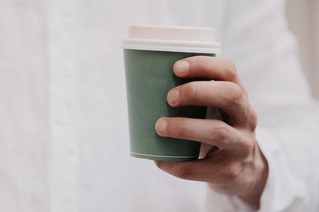 Homme tenant une tasse de café.