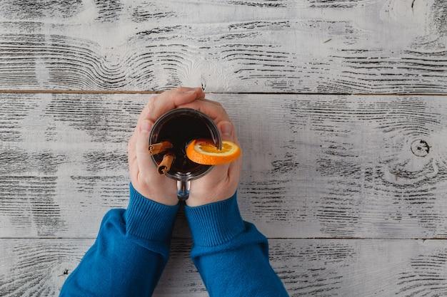 Homme tenant une tasse en verre de délicieux vin chaud de noël dans les mains, gros plan