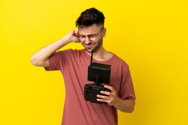 Homme tenant une télécommande de drone isolé sur fond jaune frustré et couvrant les oreilles