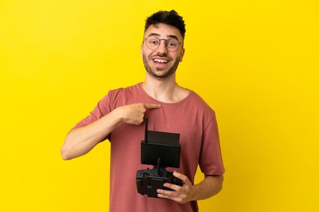 Homme tenant une télécommande de drone isolée sur fond jaune avec une expression faciale surprise