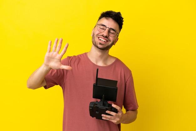 Homme tenant une télécommande de drone isolée sur fond jaune saluant avec la main avec une expression heureuse