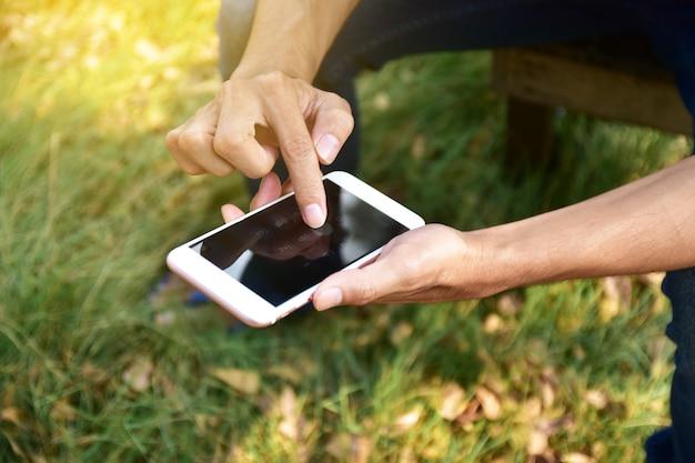 Homme tenant un téléphone intelligent mobile à l'aide d'une application intelligente par internet en ligne