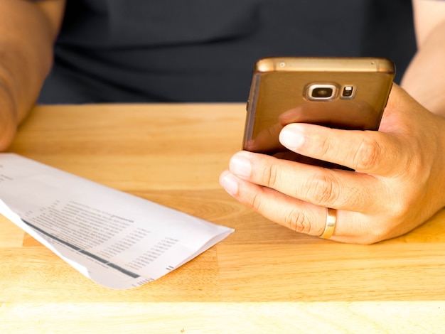 Un homme tenant un téléphone intelligent pour utiliser l'application bancaire en ligne pour payer la facture de carte de crédit.