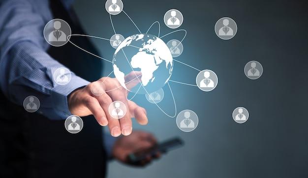 Homme tenant un téléphone intelligent avec un réseau mondial et social