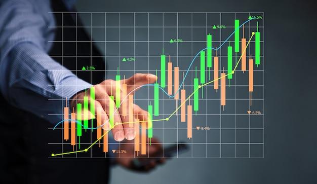 Homme tenant le téléphone avec le marché boursier