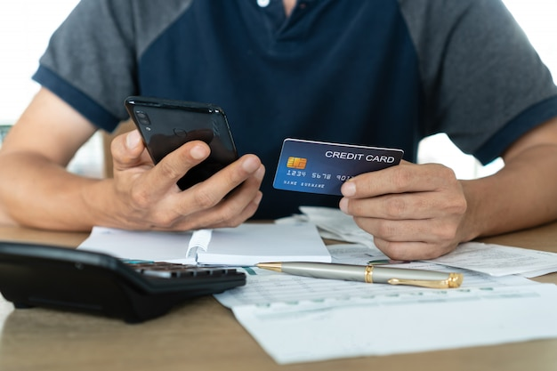 Homme tenant un téléphone mobile et des cartes de crédit, un compte et un concept d'épargne.