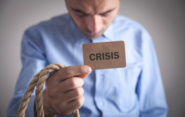 Homme tenant un texte de crise sur une carte en carton.